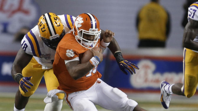 Clemson quarterback Tajh Boyd (10) is tackled by LSU defensive tackle Bennie Logan (18) during the second half of the Chick-fil-A Bowl NCAA college football game, Monday, Dec. 31, 2012, in Atlanta. (AP Photo/David Goldman)