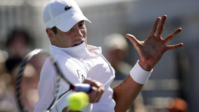 John Isner, of the United States, returns the ball to Ivan Dodig, of Croatia, during the Sony Open tennis tournament, Saturday, March 23, 2013, in Key Biscayne, Fla. (AP Photo/J Pat Carter)