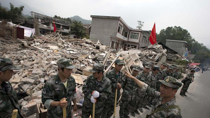 Rescue workers prepare to enter an area devastated by an earthquake in Gucheng village in Longmen county of southwestern China's Sichuan province, Sunday, April 21, 2013. Rescuers and relief teams struggled to rush supplies into the rural hills of China's Sichuan province Sunday after the earthquake prompted frightened survivors to spend a night in cars, tents and makeshift shelters. (AP Photo/Ng Han Guan)