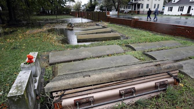 A casket floated out of the grave in a cemetery in Crisfield, Md. after the effects of superstorm Sandy Tuesday, Oct. 30, 2012. Hundreds of people were displaced by floodwaters in Ocean City and in Crisfield. At the same time, 2 feet of snow fell in westernmost Garrett County, were nearly three-quarters of residents lost power. (AP Photo/Alex Brandon)