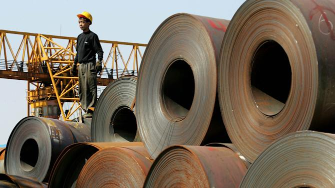 FILE - In this Nov. 18, 2004 file photo, a worker stands on a stack of rolled steel, shipped from the Baosteel factory in Shanghai destined for car manufacturers, on a dock in Guangzhou in south China's Guangdong province. China's biggest steelmaker Bapsteel Group said Thursday, Sept. 27, 2012 it has shut down a mill in Shanghai due to lack of demand in a new sign of weakening growth in the world's second-largest economy. (AP Photo/Greg Baker, File)