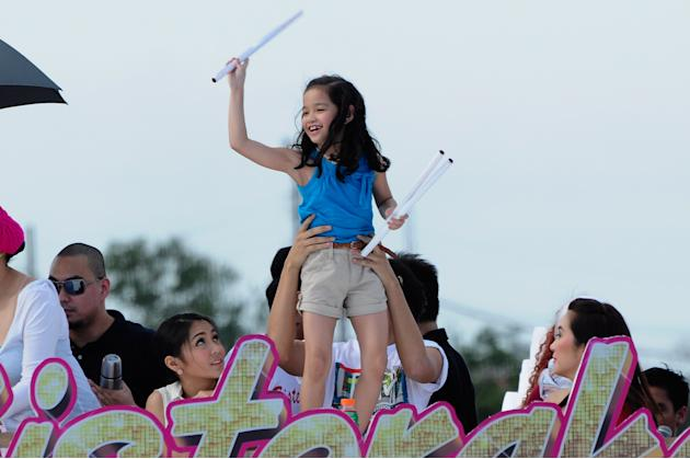 Child actress Xyriel Manabat throws posters to the crowd as the float of the movie, Sisterekas makes its way at the 2012 Metro Manila Film Festival Parade of Stars on 23 December 2012. (Angela Galia/N