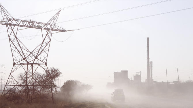 A police vehicle makes it's way toward the Lonmin Platinum mine, near Rustenburg, South Africa, Friday, Aug. 17, 2012, a day after several striking miners were shot and killed when police opened fire on the workers. (AP Photo/Denis Farrell)