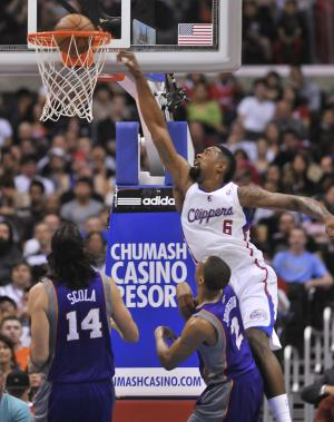 Los Angeles Clippers center DeAndre Jordan (6) throws down a dunk in front of Phoenix Suns forward Luis Scola (14), of Argentina, and forward Wesley Johnson (2) in the first half of an NBA basketball game in Los Angeles on Wednesday, April  3, 2013. (AP Photo/Richard Hartog)