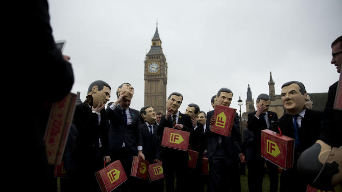 """Campaigners, wearing masks, suits and holding copies of the traditional red ministerial box to represent Britain's Chancellor of the Exchequer George Osborne on budget day, prepare to pose for the media backdropped by the Houses of Parliament as part of a campaign event in Parliament Square, London, Tuesday, March 19, 2013.  The event held Tuesday was organized by the """"IF"""" campaign to coincide with the British Finance Minister delivering his annual budget speech to parliament on Wednesday.  The """"IF""""campaign, which is a coalition of 170 charities, want the UK and G8 governments to increase agricultural aid spending to help fight poverty and hunger in developing countries.  (AP Photo/Matt Dunham)"""