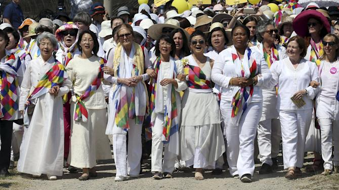 U.S. activist and feminist Gloria Steinem (4th L) and other members of the WomanCrossDMZ group march with South Korean peace activists along a barbed wire fence nearby a military check point in Paju