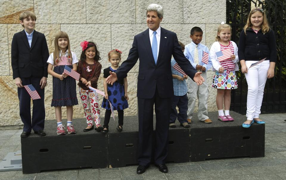 U.S. Secretary of State John Kerry poses for a photo accompanied by children at the U.S. Embassy during his visit to Bogota, Colombia, Monday, Aug. 12, 2013. Kerry is on a one-day official visit to Colombia. (AP Photo/Fernando Vergara)