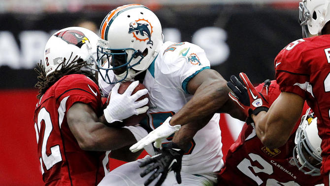 Miami Dolphins wide receiver Davone Bess, center, is tackled by Arizona Cardinals cornerback William Gay (22) and safety Adrian Wilson during the first half of an NFL football game, Sunday, Sept. 30, 2012, in Glendale, Ariz. (AP Photo/Ross D. Franklin)