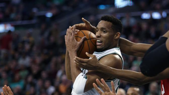 Boston Celtics' Evan Turner, top, grabs a rebound over Philadelphia 76ers' Jahlil Okafor (8) during the fourth quarter of an NBA basketball game in Boston, Wednesday, Nov. 25, 2015. The Celtics won 84-80. (AP Photo/Michael Dwyer)