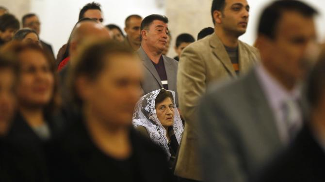 Iraqi Christians, who fled with families from violence in country, pray during mass on Christmas Eve at Saint George Victorious Cathedral in Amman