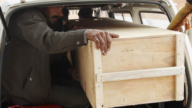 A relative sits in a van with the casket of a victim who was killed in a bomb attack, to be transported from a hospital morgue to his home in Rawalpindi