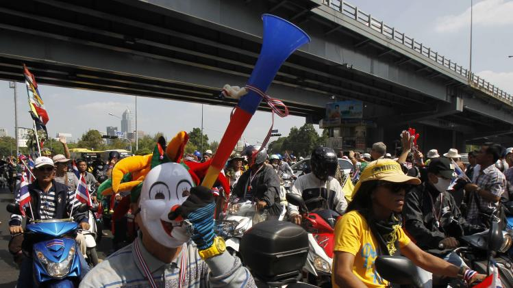 An anti-government protester wearing a mask blows a horn as he joins others in a march during a rally at a major business district in Bangkok