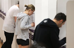 Voters fill in their ballots at a polling booth at…