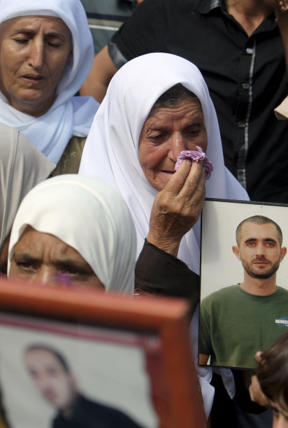 A Palestinian woman, reacts during a demonstration in solidarity with prisoners jailed in Israel in the West Bank city of Jenin, Thursday, Oct. 13, 2011.  Hamas official has provided some details about a prisoner swap deal that will free more than 1,000 Palestinians in exchange for an Israeli soldier held captive in Gaza for the past five years. The official says that out of the 450 Palestinian prisoners to be released in the first phase, some 272 will be allowed to return to their homes in the West Bank, Gaza Strip, Jerusalem and Israel. (AP Photo/Mohammed Ballas)