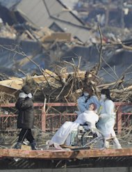 A patient in a wheelchair is helped by attendants as they evacuate from a tsunami-affected hospital at Otsuchi, northeastern Japan, on Sunday March 13, 2011, two days after a powerful earthquake and tsunami hit the the country's northeastern coast.