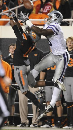 Oklahoma State's Brodrick Brown, left, and Kansas State's Chris Harper, right, reach for a pass during the second quarter of an NCAA college football game in Stillwater, Okla., Saturday, Nov. 5, 2011. Oklahoma State defeated Kansas State 52-45. (AP Photo/Brody Schmidt)