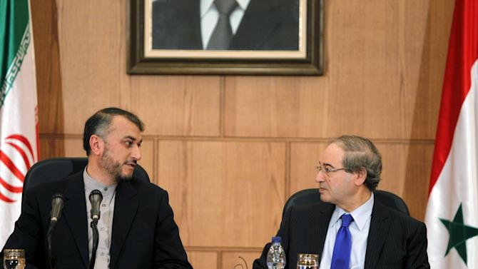 Iran's Deputy Foreign Minister Amir-Abdollahian looks at his Syrian counterpart Mekdad during a joint news conference in Damascus