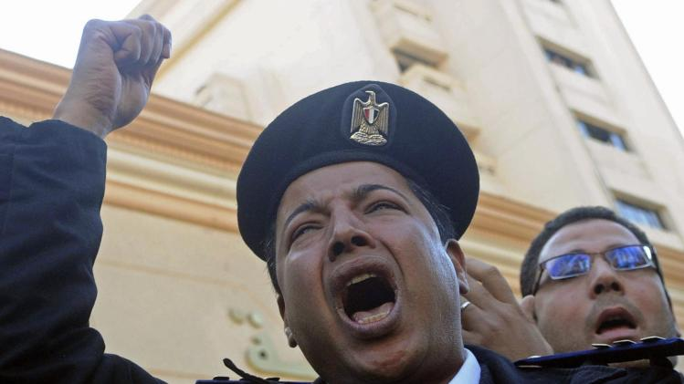 A police officer shouts slogans while taking part in a sanctioned protest outside the Interior Ministry building in Cairo