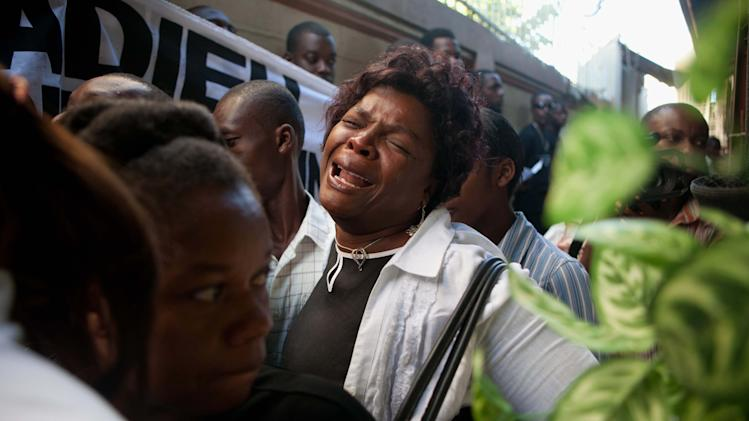 A woman cries at the funeral of 21-year-old Rooldine Lindor in Port-au-Prince, Haiti, Wednesday July 27, 2011. The Haitian college student, who was studying computer science in the Dominican Republic, was robbed, raped and murdered in her search for an apartment in Santo Domingo on July 12. Two Dominican men have been arrested in connection with her death. (AP Photo/Eduardo Verdugo)