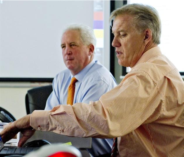 In this photo provided by the Denver Broncos, head coach John Fox, rear, and executive vice president of football operations John Elway, right, monitor the NFL football draft in the Broncos' draft roo