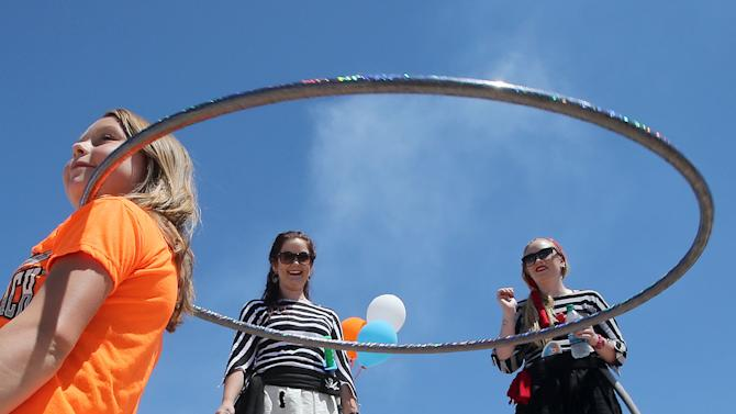 Emily Mills, left, shows off her hula-hoop skills as Jess Burch and Heather Cook look on during tourism appreciation day at the M.B. Miller County Pier in Panama City Beach, Fla., Wednesday, May 6, 2015. (Andrew Wardlow/News Herald via AP)  MANDATORY CREDIT