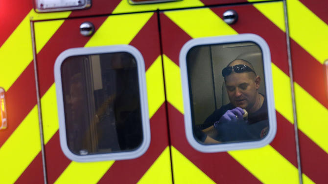 An EMT works in the back of an ambulance as it leaves an Suwanee, Ga., subdivision after an explosion and gunshots were heard near the scene where a man was holding four firefighters hostage Wednesday, April 10, 2013. A police spokesman said the suspect was dead and none of the hostages suffered serious injuries. (AP Photo/John Bazemore)