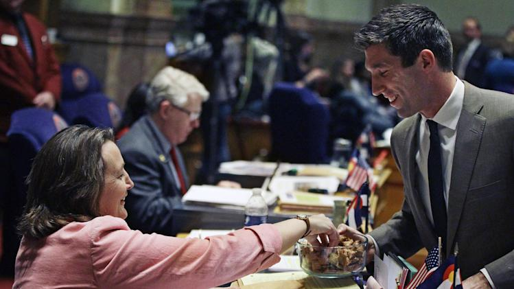 Colorado Senator Owen Hill, right, passes around a bowl of snacks to his fellow senators, including Senator Ellen Roberts, inside the senate chamber on a day in which debate and voting on several gun control bills promised to continue into the night, at the State Capitol, in Denver, Friday March 8, 2013. Colorado Democrats are on the cusp of advancing gun-control proposals Friday in a state balancing a history of heartbreaking shootings with a Western heritage where gun ownership is treasured by many. (AP Photo/Brennan Linsley)