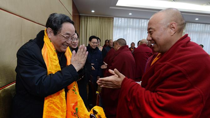 In this Jan. 8, 2013 photo released by China's Xinhua News Agency, Yu Zhengsheng, left, a Standing Committee member of the Political Bureau of the Communist Party of China (CPC) Central Committee, is greeted by a participant during a seminar held with Tibetan Buddhist representatives in Ganzi Tibetan Autonomous Prefecture, southwest China's Sichuan Province. Yu visited Ganzi at the center of the self-immolations, urging Buddhist clergy to be patriotic and denouncing the Dalai Lama. Chinese authorities are responding to an intensified wave of Tibetan self-immolation protests against Chinese rule by clamping down even harder — criminalizing the suicides, arresting protesters' friends and even confiscating thousands of satellite TV dishes. (AP Photo/Xinhua, Ma Zhancheng) NO SALES