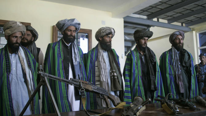 FILE - In this Sunday, May 13, 2012 file photo, former Taliban fighters hand over their weapons to Afghan police as part of a reconciliation process in Herat, Afghanistan. As the United States and its allies try to negotiate a peace settlement with the Taliban before all combat troops leave Afghanistan in 2014, a new obstacle has arisen: Insurgent splinter groups opposed to the deal are emerging, complicating U.S. hopes of leaving behind a stable country.(AP Photo/Hoshang Hashimi, File)