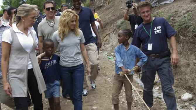 FILE - In this Sunday, April 11, 2010 file photo, Colombian singer Shakira, center left, and U.S. actor Sean Penn, right, walk with children during a visit to the makeshift camp in the Petionville Golf Club in Port-au-Prince, Haiti. The actor who stormed onto the scene of one of the worst natural disasters in history two years ago has certainly not lost interest. Defying skeptics, he has put down roots in Haiti, a country he hadn't even visited before the January 2010 earthquake, and has become a major figure in the effort to rebuild. (AP Photo/Ramon Espinosa)