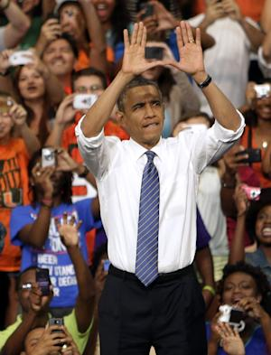 """President Barack Obama does the sign of """"The U"""" as he arrives a campaign event at the University of Miami, Thursday, Oct. 11, 2012, in Coral Gables, Fla. (AP Photo/Lynne Sladky)"""