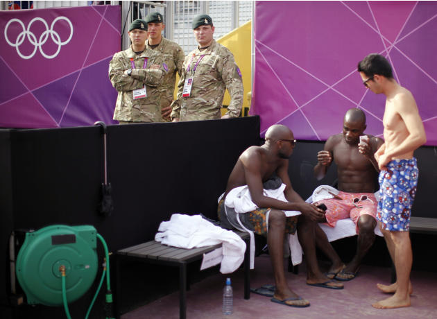 British soldiers stand guard next to dancers awaiting their turn to perform between beach volleyball matches at the London 2012 Olympic Games at Horse Guards Parade