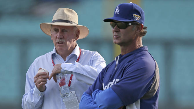 Los Angeles Dodgers manager Don Mattingly, right, talks with former Australian cricket captain Ian Chappell while the Dodgers train in Sydney, Thursday, March 20, 2014. The Diamondbacks and the Los Angeles Dodgers open the Major League Baseball regular season with games on Saturday and Sunday. (AP Photo/Rick Rycroft)