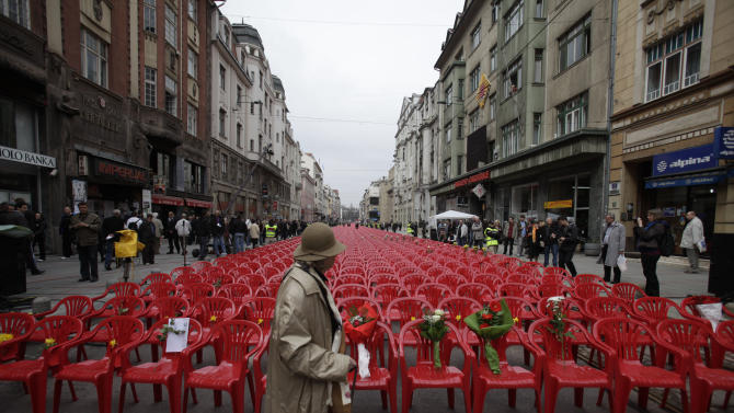 Red chairs are displayed along a main street in Sarajevo as the city marks the 20th anniversary of the start of the Bosnian war on Friday, April,6, 2012. City officials have lined up 11,541 red chairs arranged in 825 rows along the main street that now looks like a red river representing the 11,541 Sarajevans who were killed during the siege.(AP Photo/Amel Emric)
