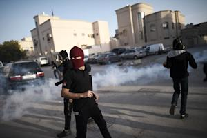 Bahraini protesters run for cover during clashes with…