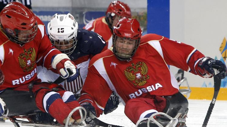 Landeros of the U.S. fights for the puck with Russia's Shikhov and Varlakov during the gold medal sledge hockey game at the 2014 Sochi Winter Paralympic Games