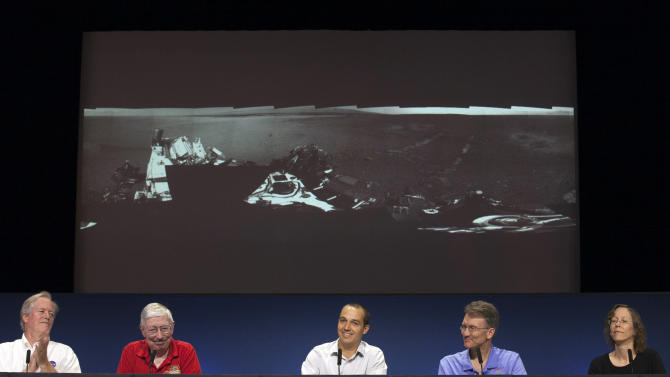 NASA scientists show a panoramic image of the Curiosity touch-down area Bradbury Landing, named after writer Ray Bradbury, showing the first tracks of the rover movements, at the Jet Propulsion Laboratory in Pasadena, Calif., Wednesday, Aug. 22, 2012. The six-wheel rover made its first test drive on Wednesday as a warm-up for the long trek to the mountain expected later this year. Shown from left: Dr. Michael Meyer, lead scientist for the Mars Exploration program at NASA Headquarters; Peter Theisinger, MSL project manger, NASA JPL, Pasadena; Matt Heverly, Lead Curiosity Driver; Roger Wiens, principal investigator of ChemCam and Joy Crisp, MSL deputy project scientist. (AP Photo/Damian Dovarganes)