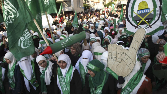 Palestinian supporters of Hamas hold signs and a model of a M75 long-range rocket during a rally to celebrate the 25th anniversary of the Hamas militant group, in the West Bank city of Nablus, Thursday, Dec. 13, 2012. Hamas supporters rallied in the first display of force by the Islamic militant group in the West Bank since it overran Gaza from the Western-backed party of Palestinian President Mahmoud Abbas in 2007. (AP Photo/Nasser Ishtayeh)
