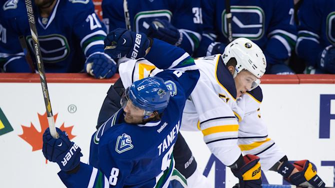 Buffalo Sabres' Nikita Zadorov, back, of Russia, checks Vancouver Canucks' Chris Tanev during the third period of an NHL hockey game Friday, Jan. 30, 2015, in Vancouver, British Columbia. (AP Photo/The Canadian Press, Darryl Dyck)