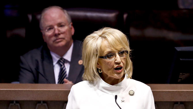 Speaker of the House Andy Tobin, R-Paulden, left, listens as Arizona Gov. Jan Brewer gives her State of the State address at the Arizona Capitol, Monday, Jan. 14, 2013, in Phoenix. (AP Photo/Ross D. Franklin)