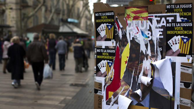 People walk past torn electoral posters calling for the independence of Catalonia following the elections in Barcelona, Spain, Monday, Nov. 26, 2012. A day after voters in Spainís economically powerful region of Catalonia dealt a punishing blow to the ruling party advocating independence from Spain, the pressure was on the party leader and regional president Artur Mas to form a new government that would carry out his promise. (AP Photo/Emilio Morenatti)