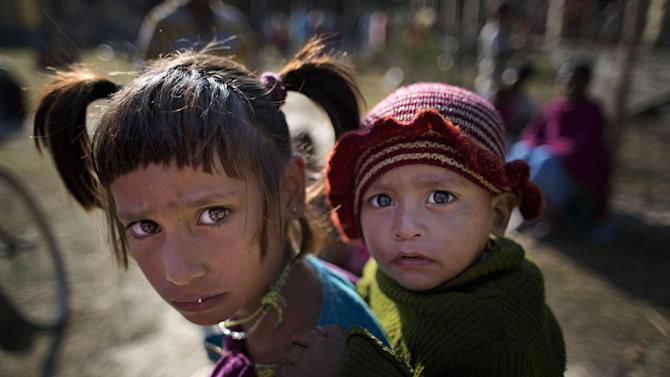 Indian tribal children react to camera at a relief camp at Tinsuti village in Sonitpur district of Indian eastern state of Assam, India, Thursday, Dec. 25, 2014. Police says the death toll from rebel violence in remote northeastern India has risen to over 70 with the recovery of more bodies from abandoned villages. Authorities have said rebels belonging to a faction of an indigenous separatist group called the National Democratic Front of Bodoland attacked tribal settlers known as Adivasi late Tuesday. Most of the Adivasis, whose ancestors migrated to Assam more than 100 years ago, work on tea plantations. (AP Photo/Anupam Nath)
