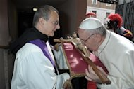 Pope Francis (R) kisses a crucifix while arriving to conduct a mass in Santa Anna church inside the Vatican, in a picture released by Osservatore Romano at the March 17, 2013. REUTERS/Osservatore Romano