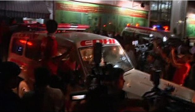 Media surround an ambulance carrying the body of Zahra Shahid Hussain, a senior female politician from cricketer-turned-politician Imran Khan's Tehreek-e-Insaf party, as it leaves a hospital in Karach