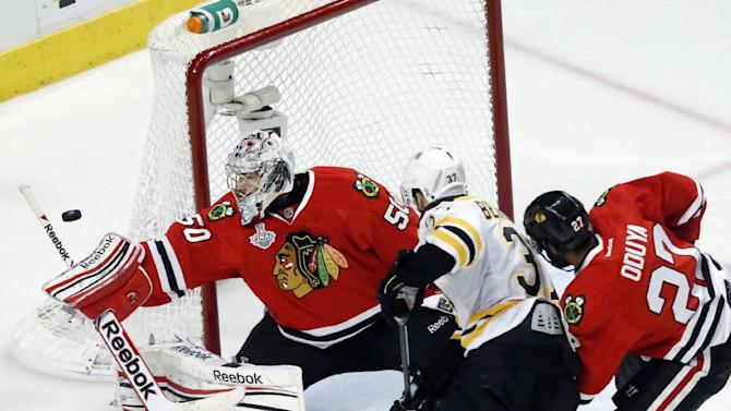 Chicago Blackhawks goalie Corey Crawford (50) makes a save during the first overtime period of Game 1 in their NHL Stanley Cup Final hockey series against the Boston Bruins, Wednesday, June 12, 2013 in Chicago. (AP Photo/Charles Rex Arbogast)