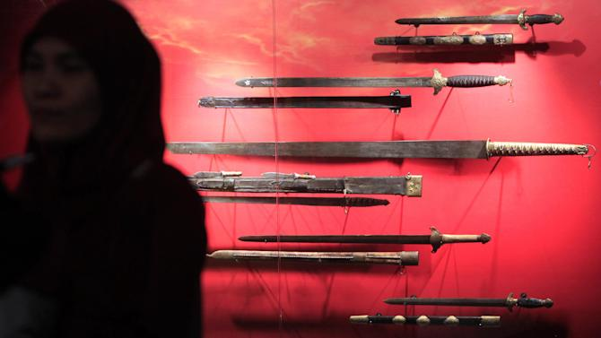 A woman stands in front of Chinese weapons of the Paleolithic period on display during the Evolution of Weapons and World Humanity Exhibition at the National Museum in Kuala Lumpur Malaysia, Saturday, Sept. 19, 2014. More than one thousand weapons from pre-historic times to modern times are on display at the exhibition. (AP Photo/Lai Seng Sin)