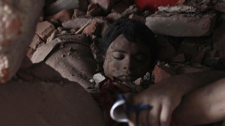 AP10ThingsToSee - A victim's body lies amid rubble at the site of a collapsed garment factory in Savar, Bangladesh,Thursday, April 25, 2013.  By Thursday, the death toll reached at least 194 people as rescuers continued to search for injured and missing, after a huge section of the eight-story building splintered into a pile of concrete. (AP Photo/A.M.Ahad)