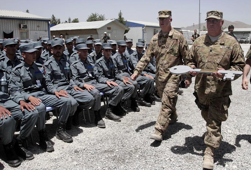 Afghan soldiers watch two U.S. Army officer carry a giant symbolic key during the fifth phase of a transfer of authority ceremony of the police academy from NATO-led troops to Afghan security forces in Kabul, Afghanistan, Saturday, June 22, 2013. (AP Photo/Rahmat Gul)