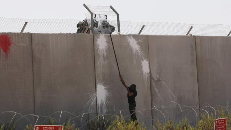 A Palestinian protester uses a metal rod at the controversial Israeli barrier during clashes with Israeli border policemen after a protest in Bilin