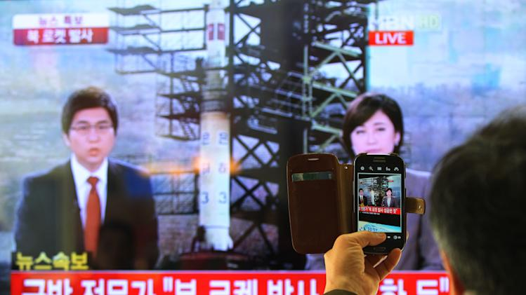 "FILE - In this Dec. 12, 2012 file photo, a South Korean man uses his smartphone to take a photo of a television screen reporting a news about North Korea's rocket launch with a banner reading: ""North Korea's rocket launch seems to be successful"" at Seoul Railway Station in Seoul, South Korea. After three nuclear tests of apparently increasing power and a long-range rocket launch that puts it a big step closer to having a missile that can carry a nuclear warhead to American shores, many believe that, in a matter of years - as little as five, maybe, though the timeframe is a point of debate - Pyongyang will have a very scary nuclear arsenal. Though it's a view not embraced by everyone, one respected South Korean expert says North Korea could be working toward 80 to 100 nuclear-tipped missiles. (AP Photo/Ahn Young-joon, File)"